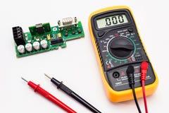 Электрический вольтамперомметр с красным цветом и чернота зондируют, дисплей показывая нул, с платой с печатным монтажом белизна  стоковые фото