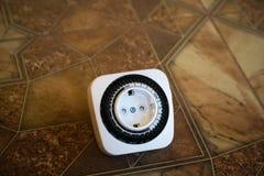 Электрический выход с таймером на коричневой предпосылке Регулировка электрического выхода с 24-часовой программой таймера стоковые изображения