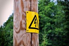 Электрический знак на деревянном столбе с расплывчатой предпосылкой стоковые изображения rf