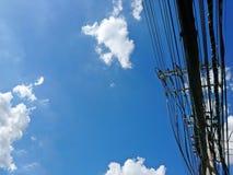 Электрический поляк высоковольтных электрических проводов и кабеля связи на предпосылке голубого неба Стоковое фото RF