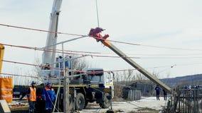Электрический поляк поднялся вверх с крюком крана деревней в зиме акции видеоматериалы