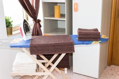 Электрический утюг и куча одежд на утюжа доске, домашнем хозяйстве стоковое изображение