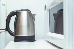 Электрический чайник и микроволна на кухонном столе стоковое изображение