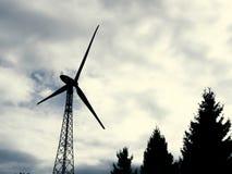 Электричество производя ветротурбину, ландшафт неба и деревья стоковое фото