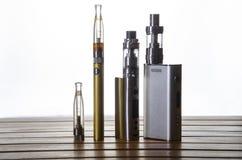 Электронные mods сигареты для ecig над деревянной предпосылкой приборы и сигарета vape стоковые изображения