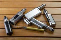 Электронные mods сигареты для ecig над деревянной предпосылкой приборы и сигарета vape стоковые фото