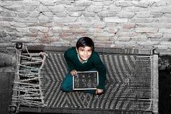 Элементарная девушка школы времени сидя на пальто стоковая фотография
