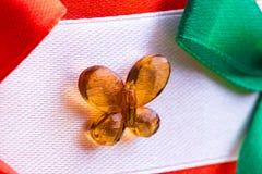 Элемент конца-вверх подарочной коробки упаковки украшения, украшение прозрачного стекла в форме бабочки на белом backg ткани Стоковое Фото