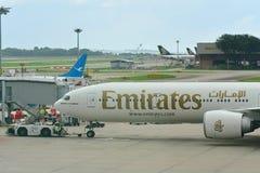 Эмираты Боинг 777-300ER будучи нажиманным назад на авиапорте Changi Стоковое Изображение RF