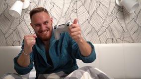 Эмоции выигрывая в видеоигре бородатого парня в спальне в зеленом купальном халате Яркие эмоции в замедленном движении человека видеоматериал