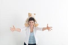 Эмоции позитва успеха Счастливая молодая женщина в белой рубашке протягивая руки вперед, хотеть обнять кто-то Кот плюша Стоковая Фотография RF