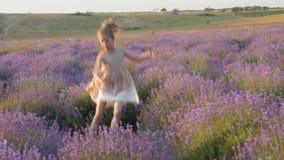 Эмоции чувств, счастье улыбки маленькой девочки весело исчезают скакать outdoors сток-видео