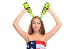Эмоциональная девушка, в американском флаге, держит 2 бутылки надземный Изолировано на белизне Стоковые Фото