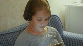 эмоциональная девушка немногая Маленькая девочка с длинными танцами волос с наушниками на доме Стоковое Изображение