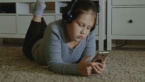 эмоциональная девушка немногая Маленькая девочка с длинными танцами волос с наушниками на доме Стоковое фото RF