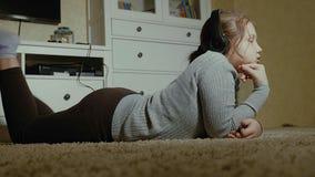 эмоциональная девушка немногая Маленькая девочка с длинными танцами волос с наушниками на доме Стоковые Изображения RF