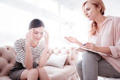 Эмоциональная женщина закрывая ее глаза пока говорящ к psychoanalyst стоковое изображение rf