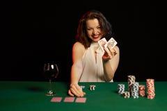 Эмоциональная молодая дама в вине белой блузки выпивая от стекла и игральных карт стоковое фото