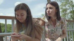 Эмоциональная молодая женщина говоря ее рассказ к ее другу, а ей не слушает, получивший SMS на сидеть мобильного телефона акции видеоматериалы