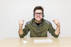 Эмоциональное изображение gamer играя игру Его команда выигрывала самое трудное сражение всегда так, что будет почему молодой чел стоковые фото