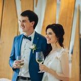 Эмоциональные красивые пары новобрачных усмехаясь на приеме по случаю бракосочетания стоковая фотография