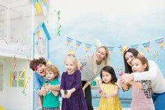 Эмоциональные матери помогая детям разрывать шутих стоковые фото