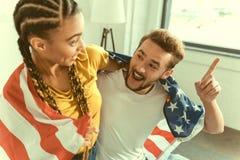 Эмоциональные молодые пары обсуждая что-то и показывать стоковое фото