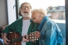 Эмоциональные старые пары разрывая с хохотом пока ослабляющ на окне стоковое фото