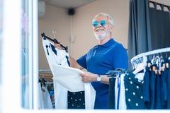 Эмоциональный пожилой клиент с брюками в руках стоковые изображения