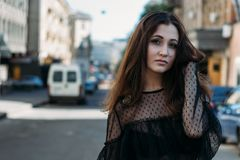 Эмоциональный портрет портрета моды стильного милой молодой женщины портрет города девушка унылая Брюнет в черном платье expectat Стоковое Фото