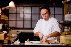 Эмоциональный шеф-повар припевая песню пока подготавливающ суши стоковые фотографии rf