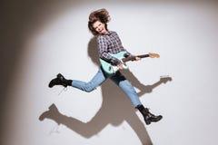 Эмоциональная женщина при гитара показывая ее язык и скакать Стоковое фото RF