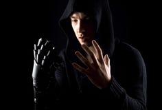 Эмоциональная, молодая и привлекательная убийца в перчатках на черноте Стоковая Фотография