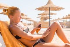 Эмоциональная тонкая женщина прикладывая масло suntan Стоковые Изображения RF