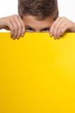 Эмоциональное брюнет мальчика в голубой рубашке с желтым листом бумаги для примечаний Стоковая Фотография RF