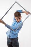 Эмоциональное брюнет мальчика в голубой рубашке с картинной рамкой в руках Стоковое фото RF