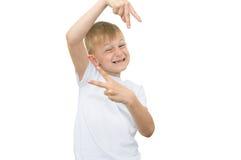 Эмоциональный белокурый мальчик в белой рубашке с серым листом бумаги для примечаний на белой предпосылке Стоковые Изображения RF