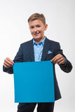 Эмоциональный мальчик подростка белокурый в голубом костюме с голубым листом бумаги для примечаний Стоковое Фото