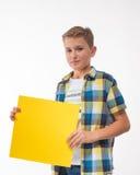 Эмоциональный подросток мальчика в рубашке шотландки с желтым листом бумаги для примечаний Стоковые Изображения RF