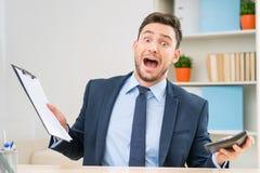 Эмоциональный работник офиса сидя на таблице Стоковые Изображения