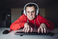 Эмоциональный gamer играет игру на домашнем компьютере Сердитый молодой человек и имеет его пальцы на клавиатуре стоковые фотографии rf
