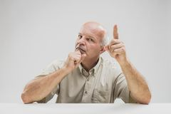 Эмфатический старший показывать с его пальцем стоковые изображения
