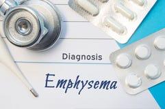 Эмфизематоз диагноза Врачуйте стетоскоп ` s, электронный термометр и 2 волдыря пилюлек лежа около пусковой площадки с надписью di Стоковые Изображения RF