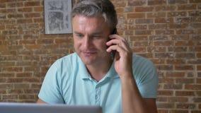 Энергичный взрослый кавказский мужчина говорит над телефоном и использует его компьютер пока сидящ в офисе, коричневом кирпиче акции видеоматериалы