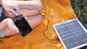 Энерги-производящ технологию, конец вверх, девушка рук соединяется от панели солнечных батарей к мобильному телефону снаружи сток-видео