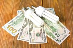 Энергосберегающая предпосылка лампы, раскаленных добела, дневных, электричество, денег, электрическая лампочка Eco, сравнение лам стоковые изображения