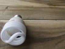 Энергосберегающая электрическая лампочка на деревянной предпосылке Стоковое Фото