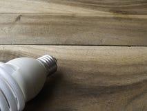 Энергосберегающая электрическая лампочка на деревянной предпосылке Стоковое Изображение