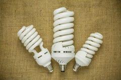 Энергосберегающая люминесцентная лампа 3 на предпосылке дерюги Стоковое Изображение RF