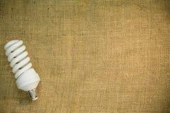 Энергосберегающая люминесцентная лампа на предпосылке дерюги Стоковая Фотография